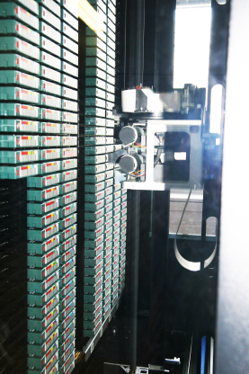 the inside of the tape robot, with shelves containing tapes on the left side, and the gripper on the right